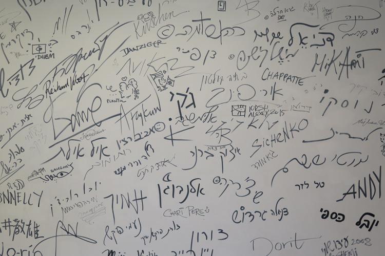 אמנים חותמים על קיר במוזיאון