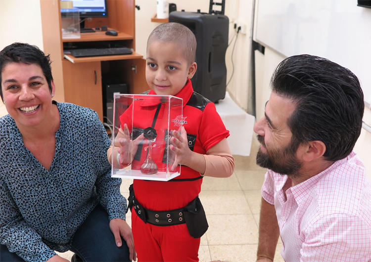 דור והילה שותפתו מעניקים בובה לאחד הילדים