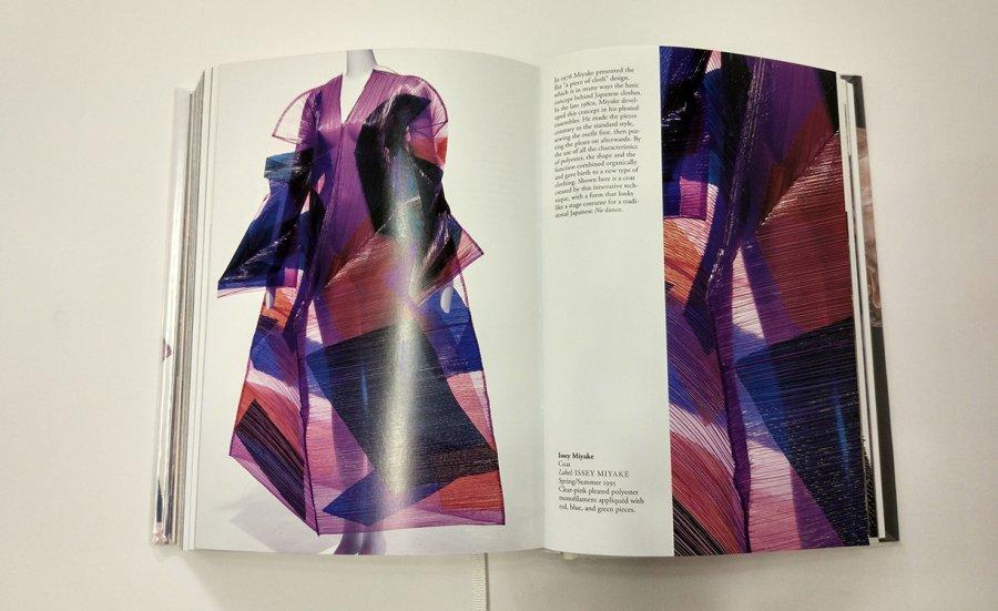 אופנה יפנית, Issey Miyke ,Coat. איסי מיאקי, שמלת אביב/קיץ 1995, בד פוליאסטר סינטטי ורוד שקוף מקופל ביחד עם חתיכות אדום, כחול וירוק. השמלה מזכירה בצורתה לבוש במה של תיאטרון No יפני עם טכנולוגיה חדשה
