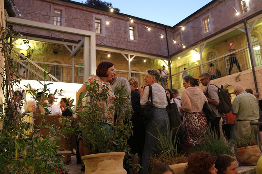 הקהל בהרמת הכוסית בחצר הפנימית בבית הנסן