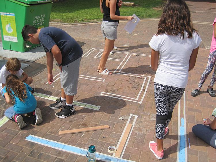 תלמידי בית הספר בשכונה עוזרים ביצירת מבוך ליד פח למיחזור על מנת לעודד מיחזור בשכונה. צילום_ אקוויק 2017