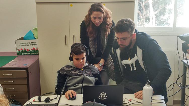סטודנט, תלמיד ומורה מגולדטק בזמן התנסות במשחק שלהם.