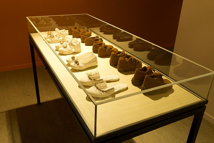 נעליים מכוסות באדמה כחלק מהמיצג של האמן פריד אבו שקרה