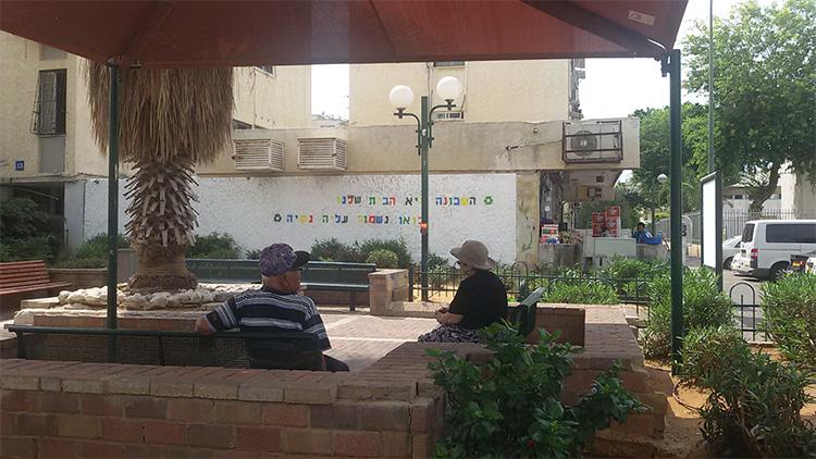 כיכר שכונתית אחרי ההתערבות של סדנת ECOWEEK: חידוש לוח המודעות וצביעת קיר עם מסרים ליד חנות מקומית. צילום: אקוויק 2017
