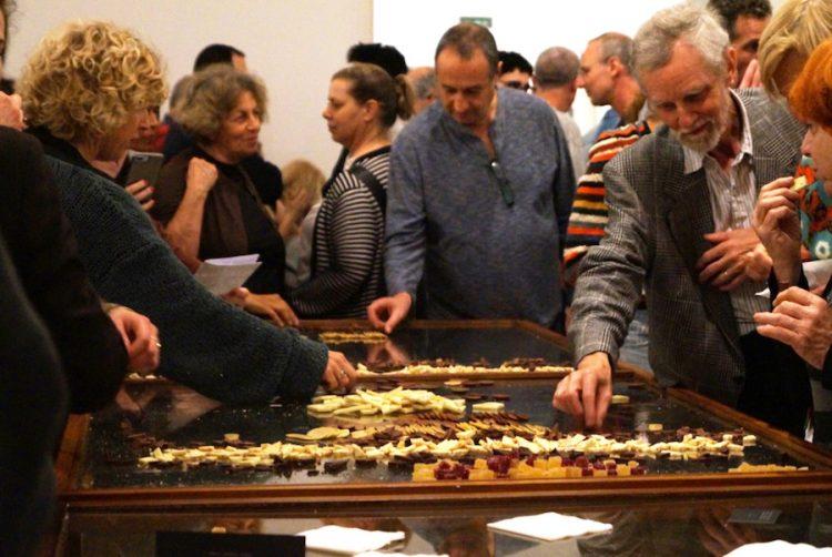 """שולחן השוקולדים יוצר דיסונאנס בין המוצגים בחדר לבין האנשים הגוהרים מעל השולחן, ומתכתבת עם עבודתו של מיכה לורי """"חיילים של שוקולד"""""""